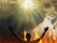man with hands raised towards clouds and sun with image of religious figure on it