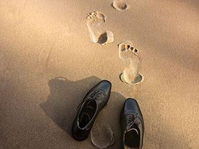 Shoes and footprints in the sand