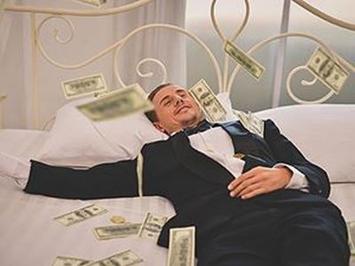 man laying in bed with money around him